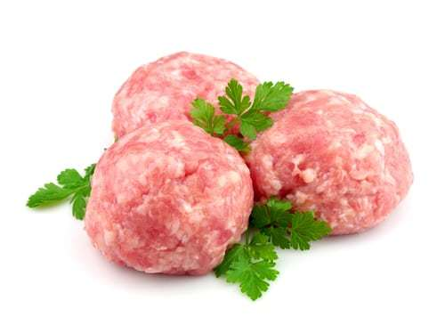 Raw meatballs with greens on a white background