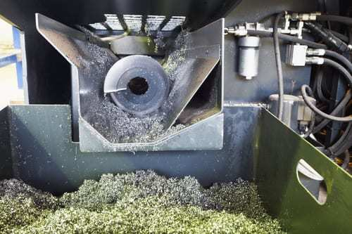 Screw conveyor in a manufacturing setting, processing green material.